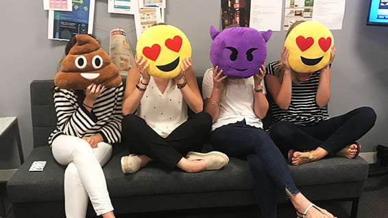 Four women sitting on couch covering their faces with emoji shaped pillows