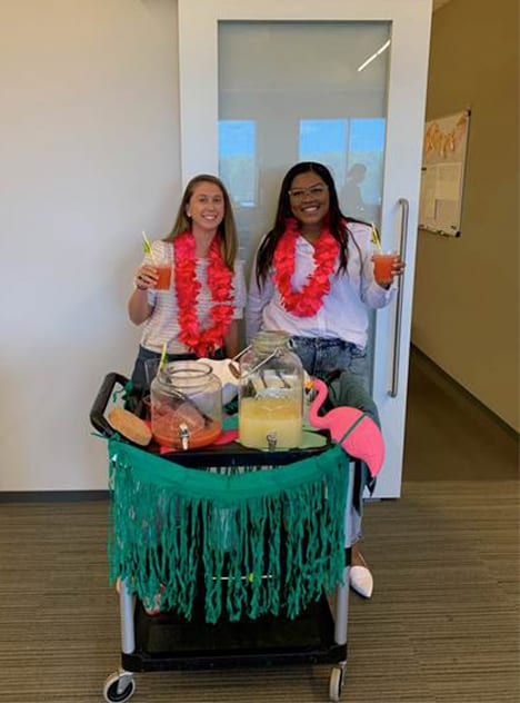 Two women holding drinks from bar cart inside the office